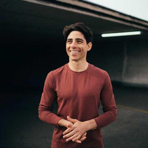 Brad steht vor einem dunklen, industriell-anmutenden Hintergrund und hält die Hände so verschränkt, als hätte er gerade geklatscht und aufgefordert, dass es losgehen soll. Er hat kurze, dunkle Haare, trägt ein langärmliges rotes T-Shirt und lächelt strahlend an der Kamera vorbei in die Ferne.
