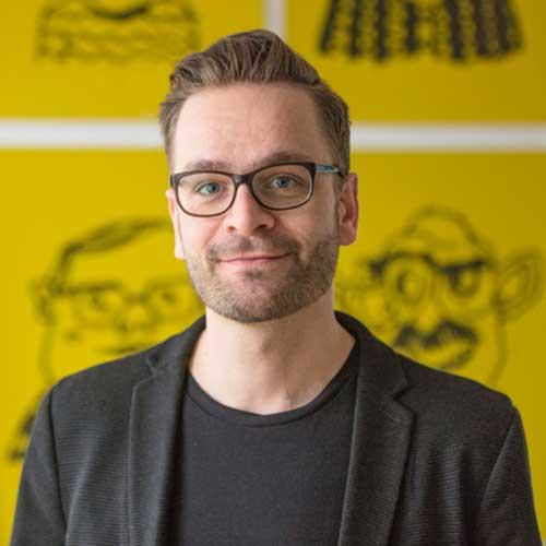 Gregor Strutz steht vor einem gelben Hintergrund mit schwarzen Illustrationen darauf. Er trägt eine Brille, kurze dunkelblonde Haare und lächelt freundlich in die Kamera.