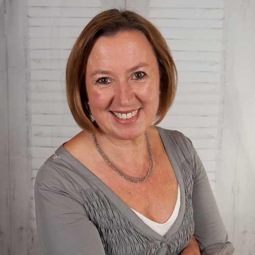 Ulrike Schimmel steht leicht seitlich zur Kamera und lächelt offen und strahlend. Sie trägt eine bestickte Tunika und eine Kette um den Hals. Ihre Haare sind kinnlang und rötlich-braun.