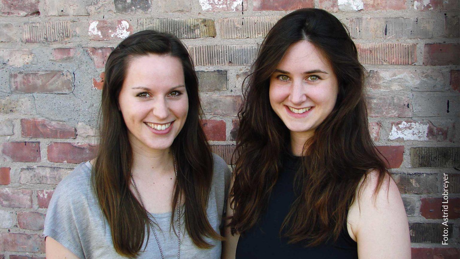Ann-Marie und Rebecca stehen vor einer Ziegelsteinwand. Es ist Sommer und beide tragen kurzärmlige Oberteile. Die beiden stehen Schulter an Schulter und lächeln fröhlich in die Kamera. Beide haben lange, dunkle Haare.