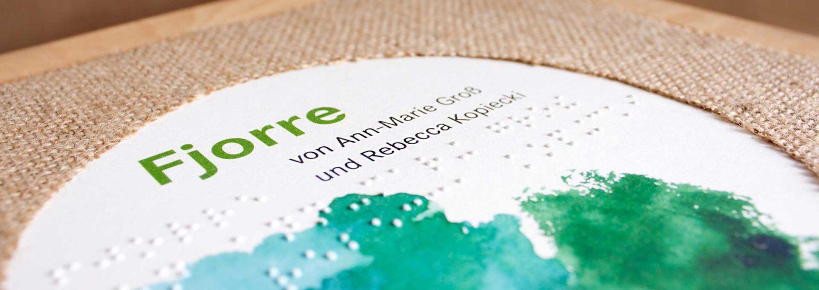 """Titelseite des Inklusiven Kinderbuchs """"Fjorre"""" von Ann-Marie Groß und Rebecca Kopiecki. Der Titel besteht aus einer Holzseite mit aufgebrachtem Text in Schwarzdruck und Braille. Um die Schrift herum ist ein Einband aus Jute angebracht."""