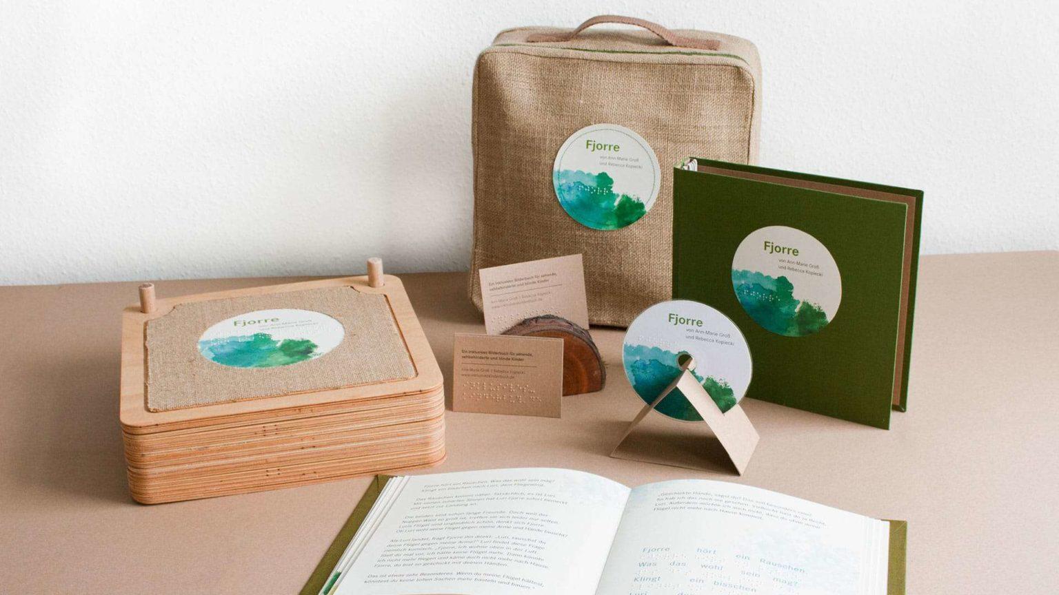 """Zu sehen ist das gesamte Paket von """"Fjorre"""", das wir im Rahmen unserer Bachelorarbeit an der HTW entwickelt haben. Das große Holzbuch, der Koffer als Verpackung, das Textbuch mit dem gesamten Text, die CD für das Hörbuch und inklusiv gestaltete Visitenkarten."""