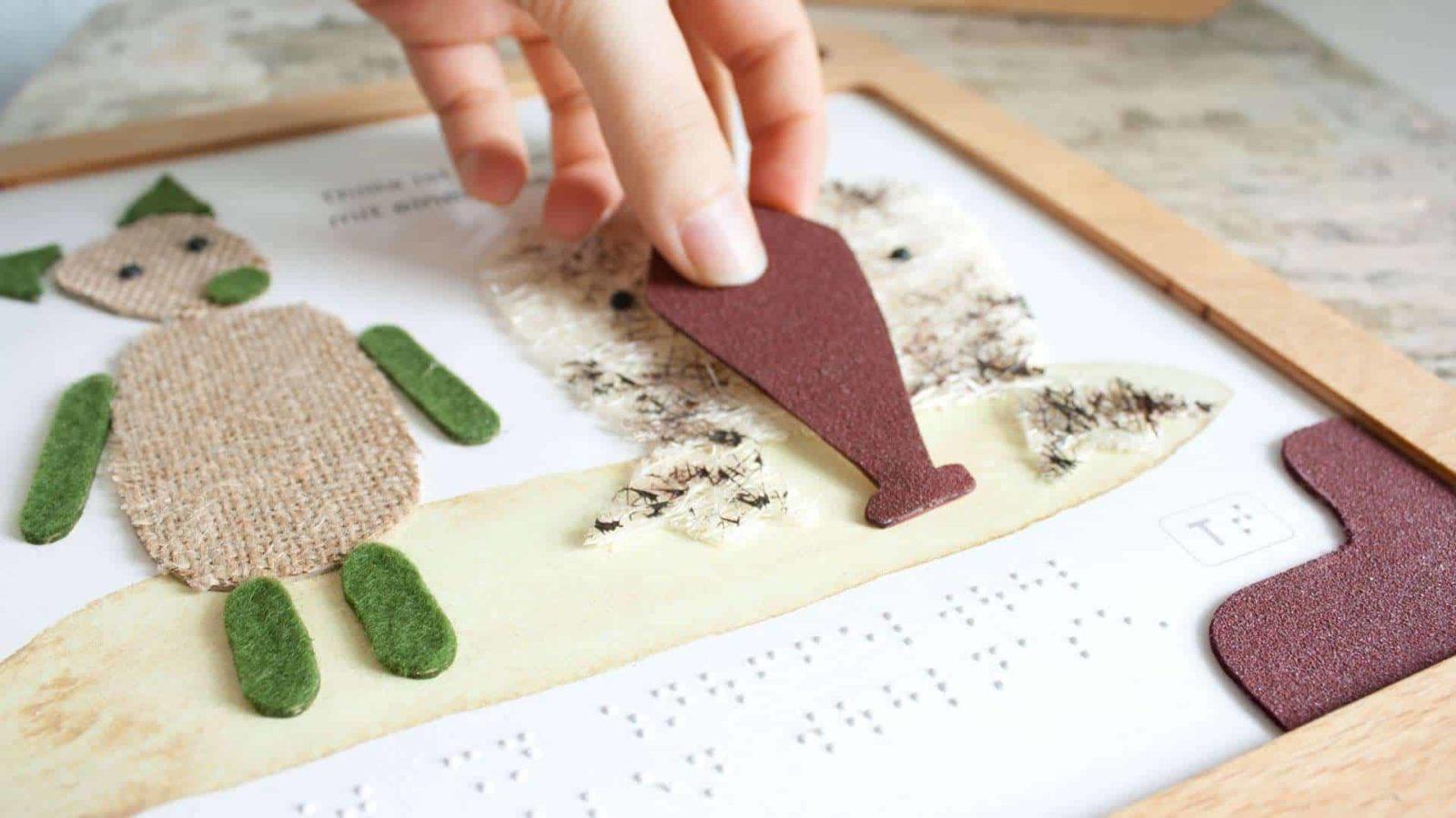 Eine Hand puzzelt Thillas Nase an die richtige Stelle. Sie ist mit Klettverschluss befestigt und kann Fjorre anprobiert werden.